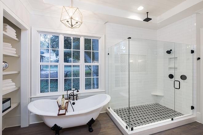 Frameless glass shower with hexagonal black and white tiled floor