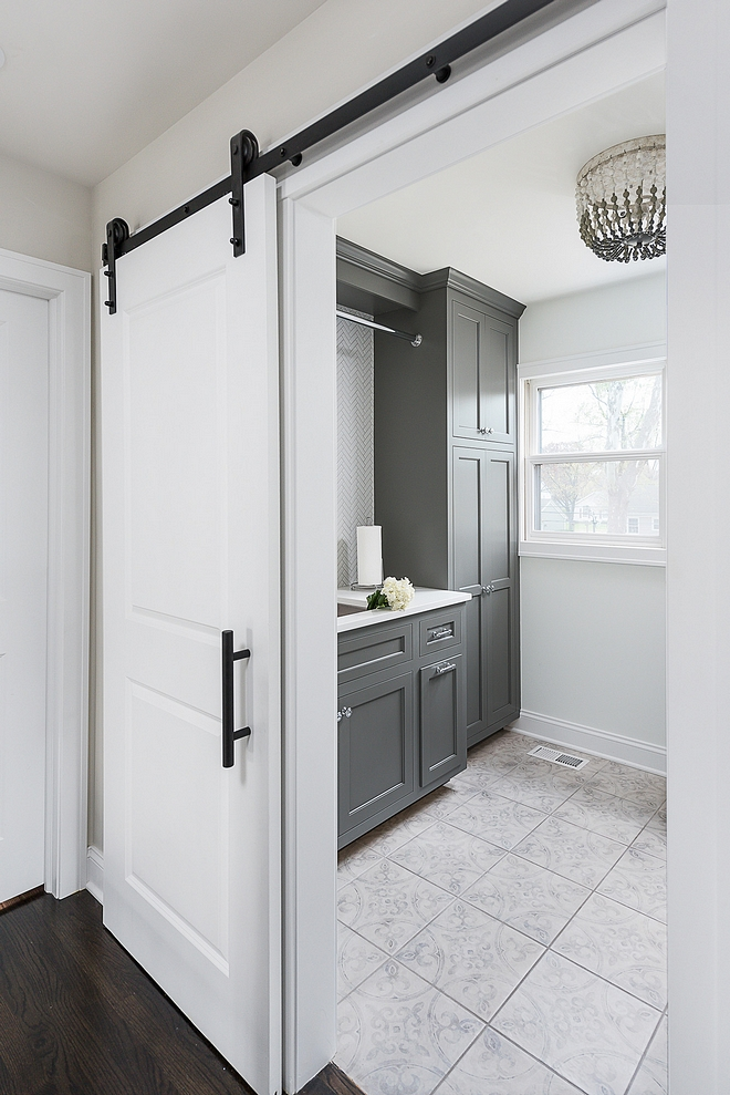 Grey laundry room Renovated Laundry room Upstairs you will find a newly-renovated laundry room with sliding barn door and dark grey cabinets. Trim, walls and barn door are painted in Benjamin Moore Super White #laundryroomrenovation #laundryroom #renovation #Greylaundryroom #RenovatedLaundryroom
