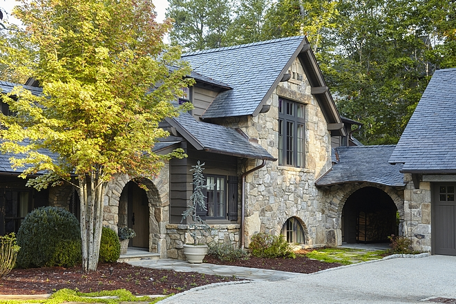 Rustic stone home exterior with Slate roof, arched breezeway Siding is undressed pine with mitered corners #rusticstonehome #stonehome #stonehomes #exterior #rusticexteriors