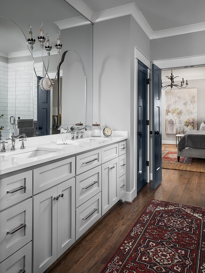 Master bathroom cabinets feature shaker style doors and drawers. Paint color is Sherwin Williams Mindful Gray. Arched mirrors are installed over a large custom mirror to give a layered feel to it #bathroomcabinet #bathroommirrors