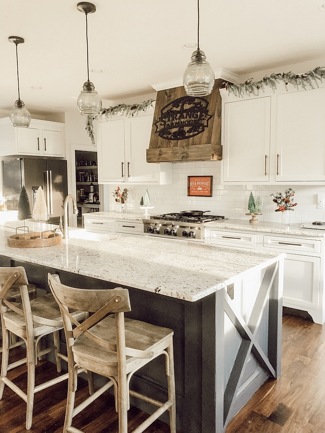A stained wooden hood and a kitchen island with X insets give a farmhouse feel to this large kitchen #farmhousekitchen #farmhouse #kitchen
