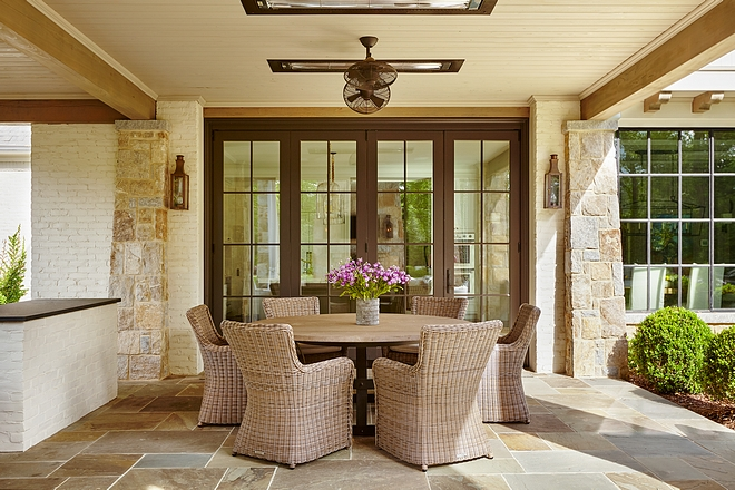 Flanked by stone columns, the retractable patio doors open to an inviting covered patio with outdoor kitchen Floor tile is Bluestone #patio #bluestone #outdoor #oudtdoors #outdoorkitchen