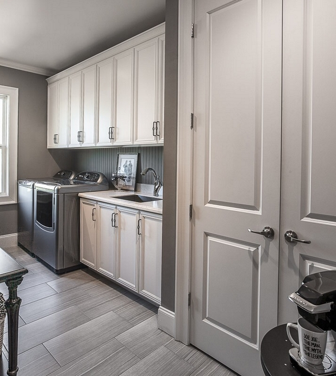 White and grey laundry room with 12x24 floor tile and beadboard backsplash Wall paint color is Martha Stewart MSL266 Cement Gray #laundryroom #MarthaStewart