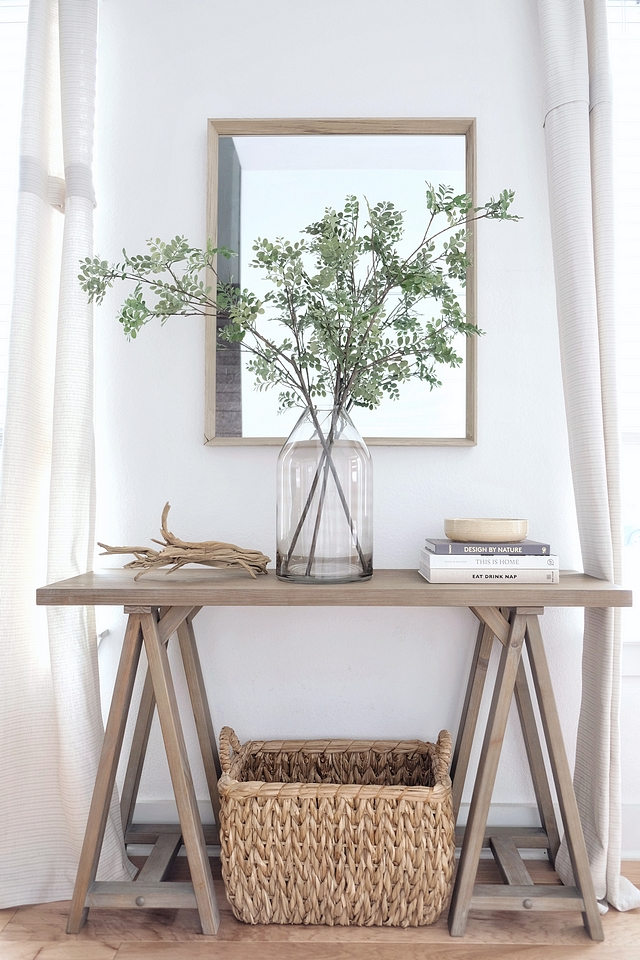 Coastal Farmhouse Foyer Console Table Wooden Mirror Woven Basket Glass Vase with Greenery and driftwood #CoastalFarmhouse #Foyer #ConsoleTable #WoodenMirror #WovenBasket #GlassVase #Greenery #driftwood