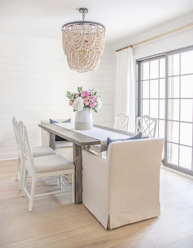 Neutral White Dining Room with White Shiplap Accent Wall, Cream beaded chandelier, Natural wood dining table, linen dining chairs and white Chippendale dining chairs #DiningRoom #Neutraldiningroom #WhiteDiningRoom #Shiplap #beadedchandelier #diningtable #linendiningchair #whiteChippendalediningchair