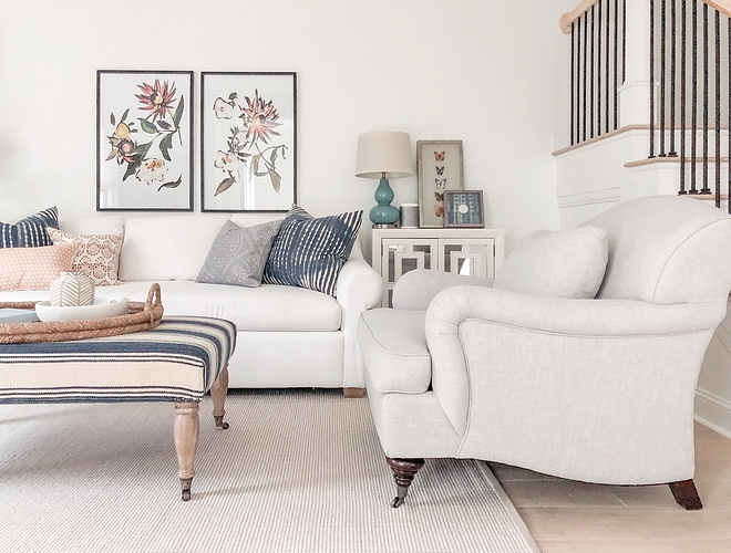Neutral Living Room White Linen Sofa with Natural Linen Accent Chair and neutral rug Pillows, framed artwork and an upholstered ottoman brings color to this neutral living room #NeutralLivingRoom #WhiteLinenSofa #NaturalLinen #AccentChair #neutralrug #Pillows #framedartwork #ottoman