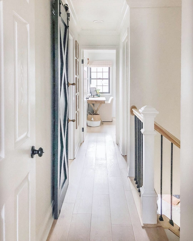 This hallway is one of my favorite transformations in the home. Previously there was a view of the half wall going up the second staircase and part of the hallway, which is now wrought iron spindles #hallway #home #staircase #wroughtironspindles