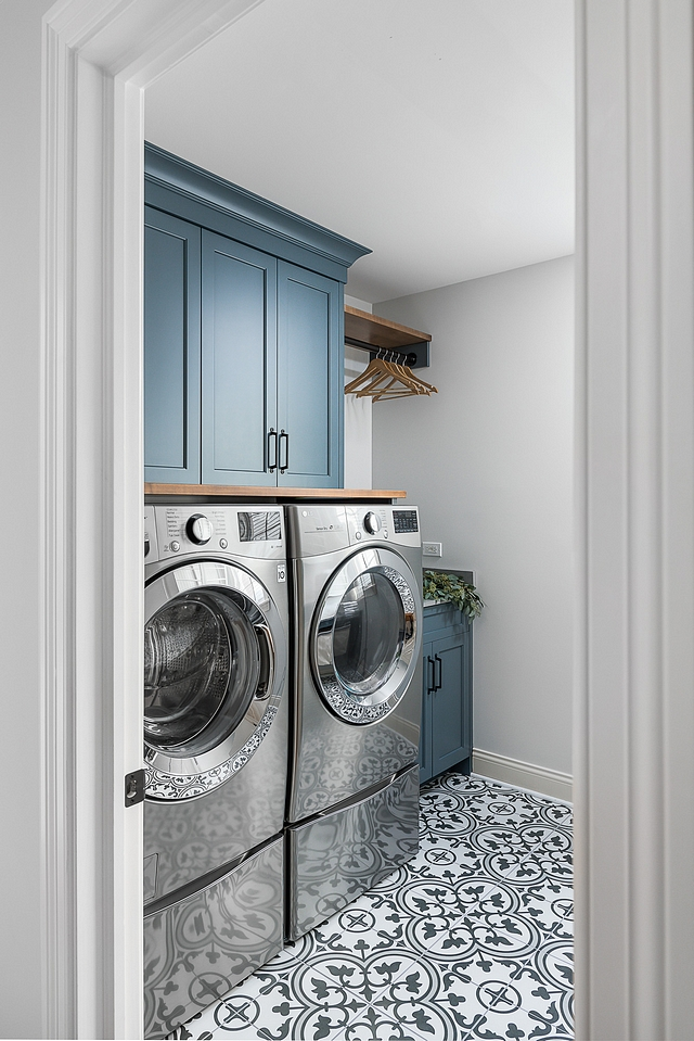 Laundry room renovation The cabinets were painted this lovely custom shade and given new doors and hardware. And in a room like a laundry room, why not go fun and bold with the flooring? We selected this tile that mimics the look of more expensive cement tiles #laundryroom #renovation #cabinet #paintingcabinets #cementtile