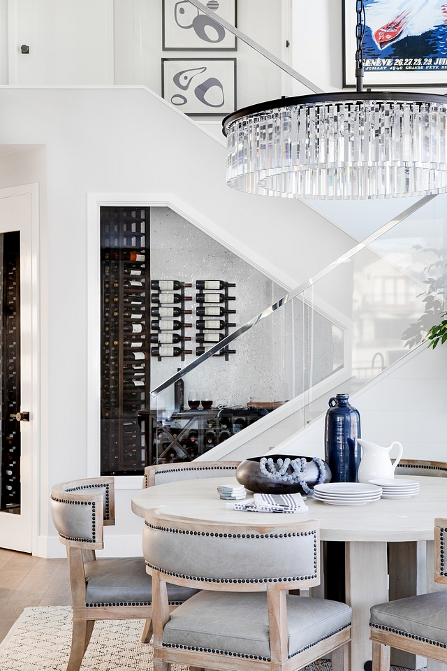 Winer Cellar Dining Room with Wine Cellar The dining room feels inviting with a round dining table and a comfy rug. Also notice the sleek staircase with glass railing and the beautiful wine cellar #winecellar #diningroom #glassrailing