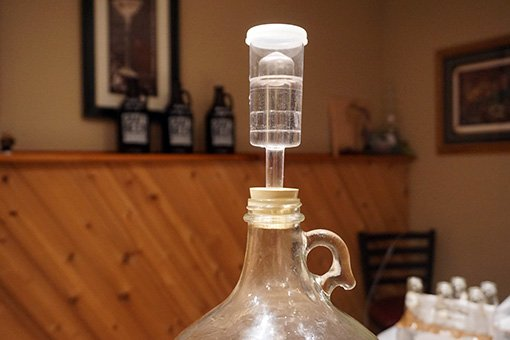 A plastic three piece airlock fitted to a one gallon carboy full of fermenting cider