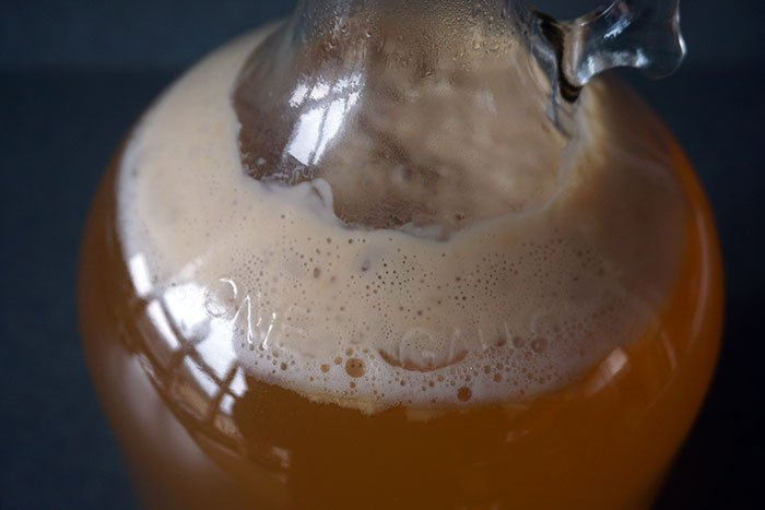 brown foam krausen forming on the top of cider in fermentation