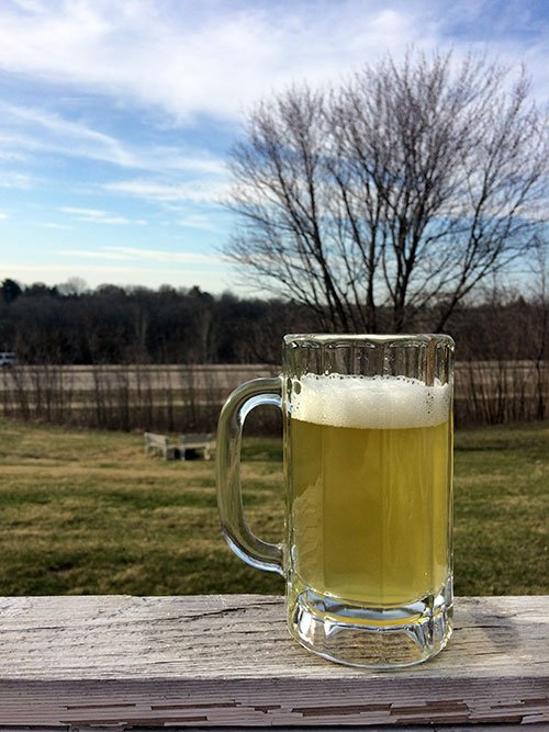 a mug of cider with white head sitting on a deck railing outside