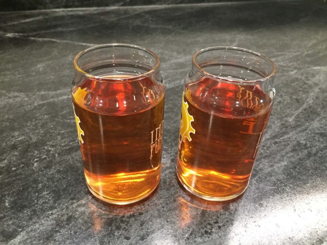 two sample glasses filled with blueberry hard cider that look identical