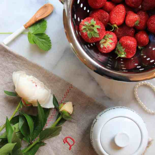 fresh indoor strawberries in a metal colander on a marble countertop with a white peony