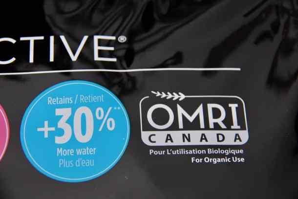 white OMRI-listed logo on black garden organic fertilizer bag indicating safe for organic use