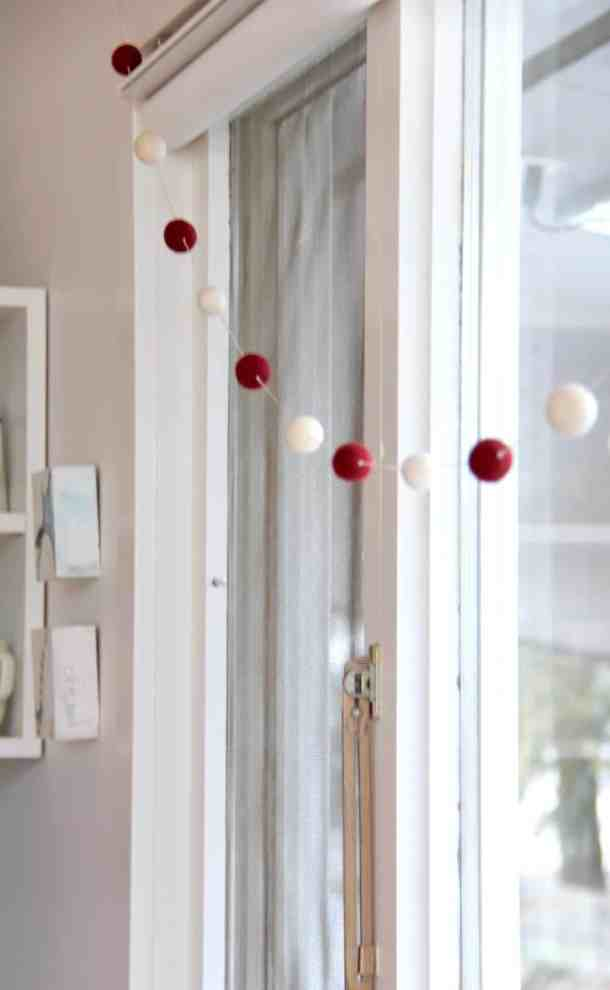 Make this felt ball garland this year! It's an easy holiday craft for a Christmas garland that you can DIY yourself. Try making this felt pom pom garland! #pompomgarland #feltballgarland #woolpompomgarland #feltgarland