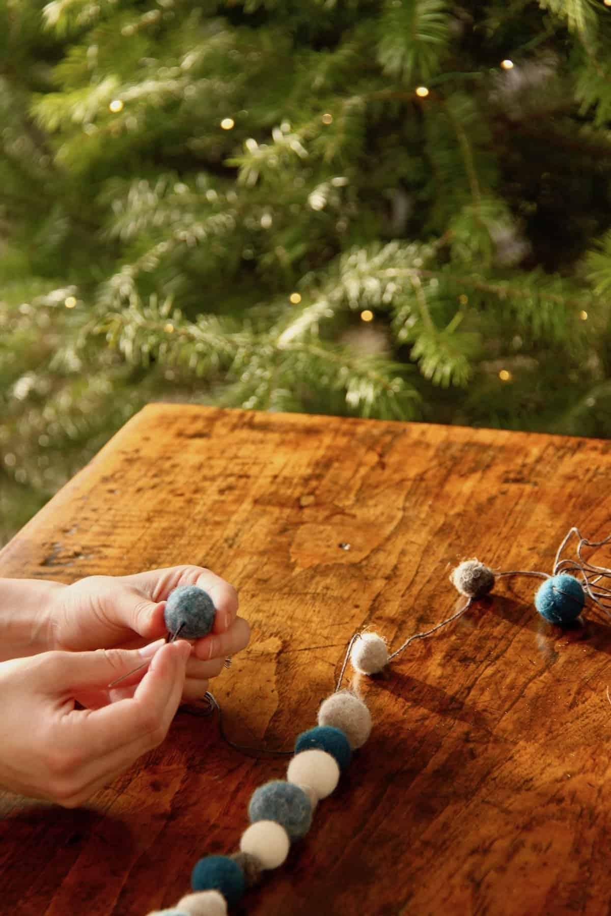 Here's how to make a felt pom pom garland for the holidays or for decor. This tutorial shows exactly how a felt ball garland is made, including detailed instructions. #feltgarland #feltballgarland #pompomgarland #feltpompoms
