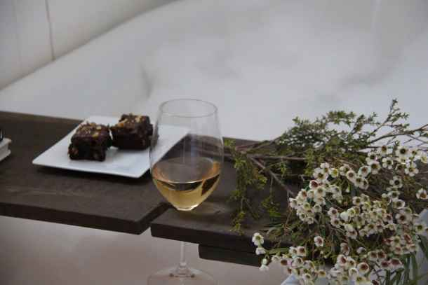 Bubble bath tub tray with wine glass, brownies, and cut flowers