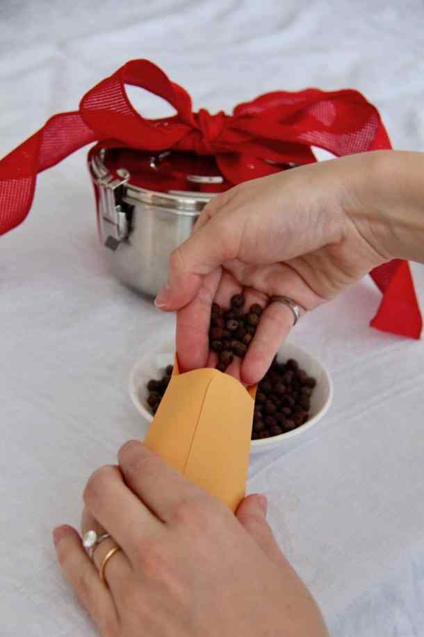 two hands pouring seeds into a small envelope to make a DIY valentine gift