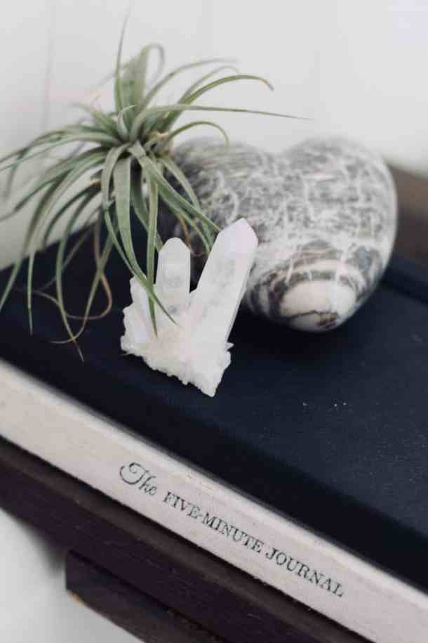 two journals on a bath caddy topped with a green air plant, marble stone heart, and white quartz crystal for spa bathroom decor