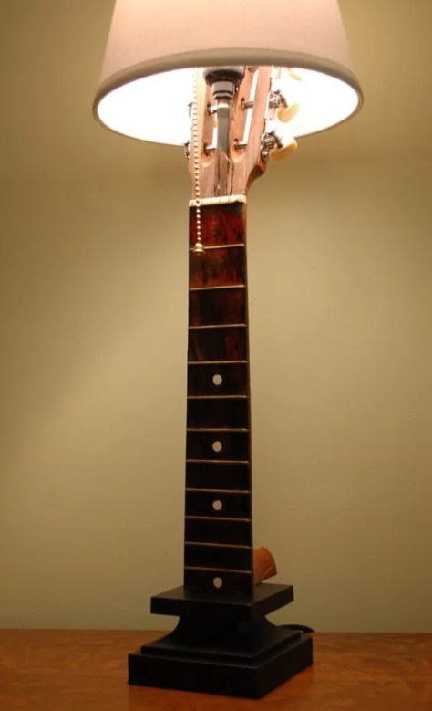 Homelysmart 9 ways to upcycle old guitars into things that youll only the fret board and the guitar head are used to create this table lamp the fret board is fixed on a wooden stand while the lamp and the lamp shade is aloadofball Images