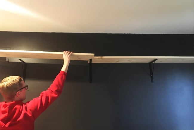 Make a DIY wall to wall shelf without having to use wall length boards. We show you how to use shorter boards but still create a seamless modern shelf!