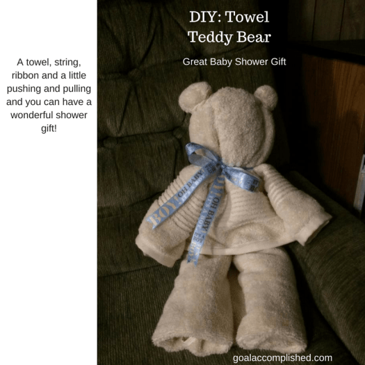 Teddy Bear made out of towel, sitting in chair. Blue ribbon around neck.Text: Towel Teddy Bear: Great Baby Shower Gift, homeschoolchristianmom.com