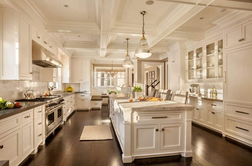 30 Custom Luxury Kitchen Designs that Cost More than  100 000 Massive white kitchen with ornate coffered ceiling in galley layout with  large center island