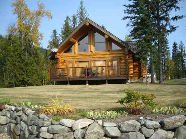 Cabin style log home with small deck on large sloping lot.