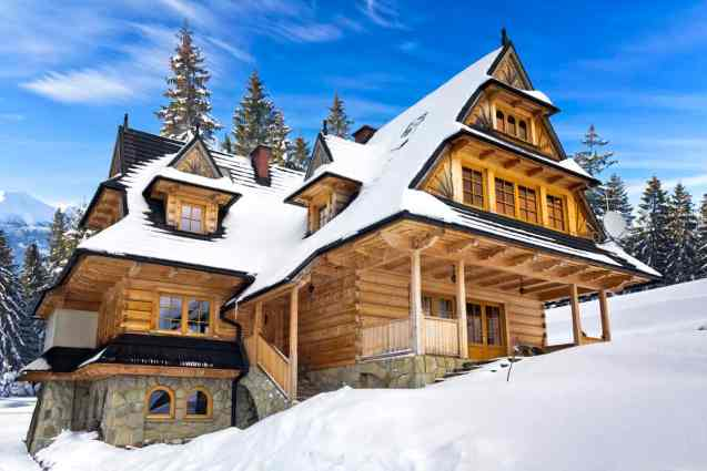 Ski chalet log mansion with stone exterior set up high in mountains on snowy slope.