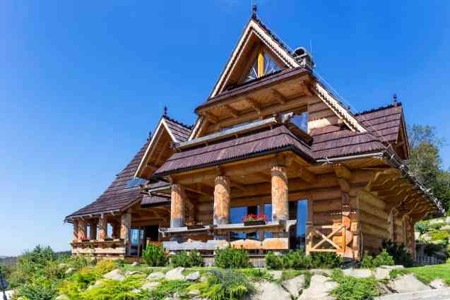 Magnificent log home mansion with huge beams on deck supporting upper floors on top of a mountain.