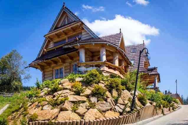 Gingerbread house like fairy tale log home with round veranda perched on top of rock outcropping.