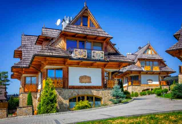 Intricate 3-story log home house on hill with incredible view.