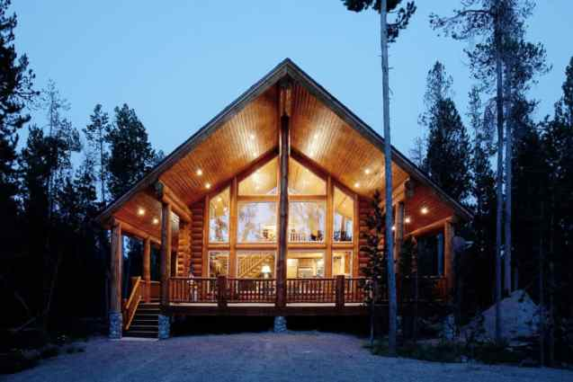 Contemporary A-frame log home chalet with huge overhang gabled roof overhanging huge deck. Massive 2.5 story window.