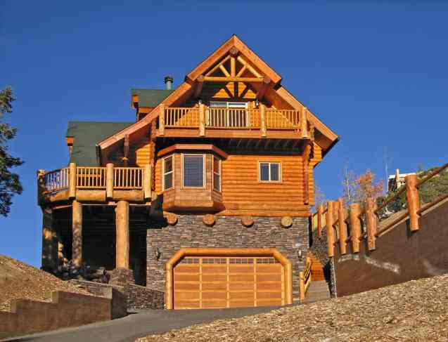 Side view of log home with double car garage, crow's nest balcony and large log beams supporting deck.