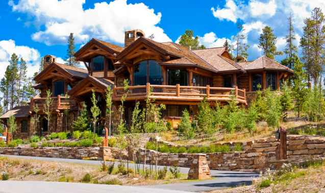 Incredible ski chalet log mansion with huge picture window and massive sun deck on sloping property with gorgeous front yard gardens.