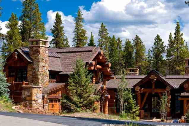 Ski community log chalet with tall stone chimney.
