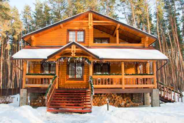 Swiss style log home chalet with upper balcony and wide porch set among trees with snow on the ground.