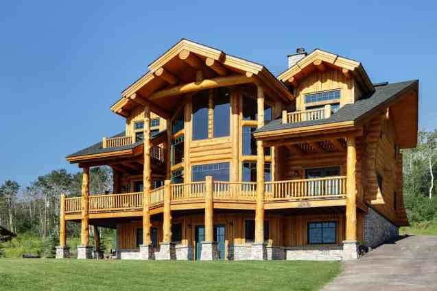 3 story log home with full-width deck on sloping property