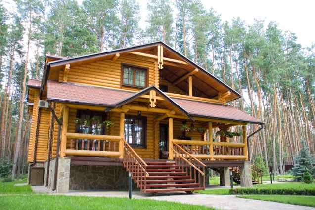 Wide log home with full width covered porch elevated on large grassy lot.