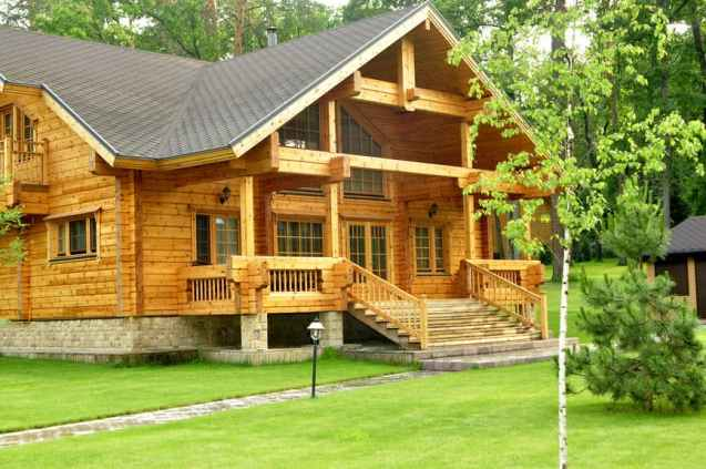 elegant wide log home with staircase rising up to wide covered porch and front door.