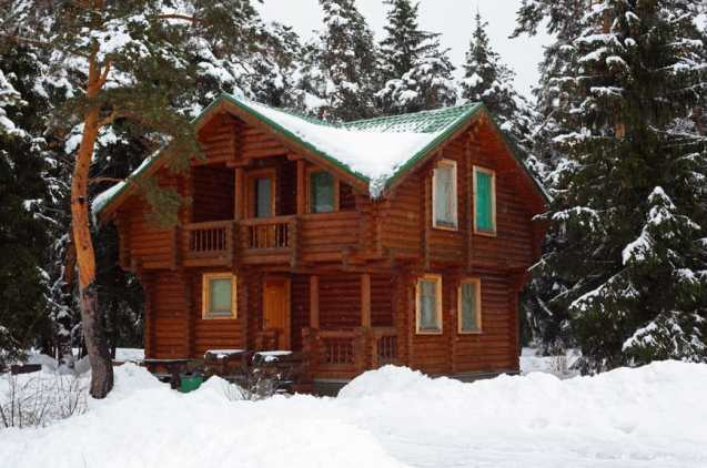 Dark log home (small) in forest setting with piles of snow on the ground.
