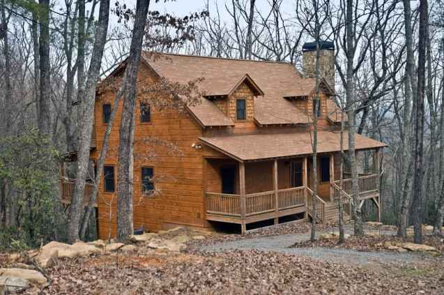 Suburb log home with dormers and covered porch.