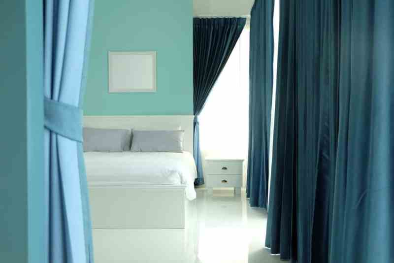 Blue bedroom with blue floor-to-ceiling curtains for privacy.