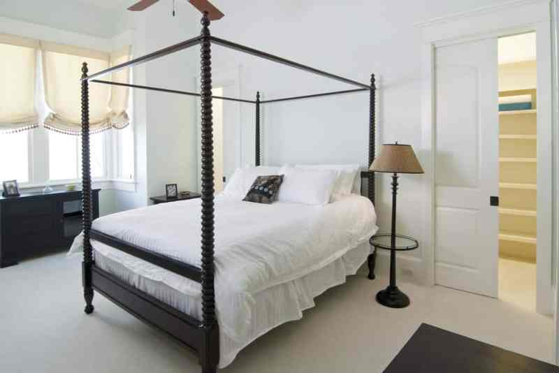 White bedroom with four-poster bed and a pocket door.