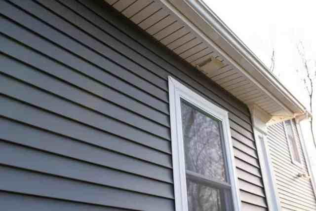 Bir evin dış koyu gri vinil dış cephe kaplaması kapatın.