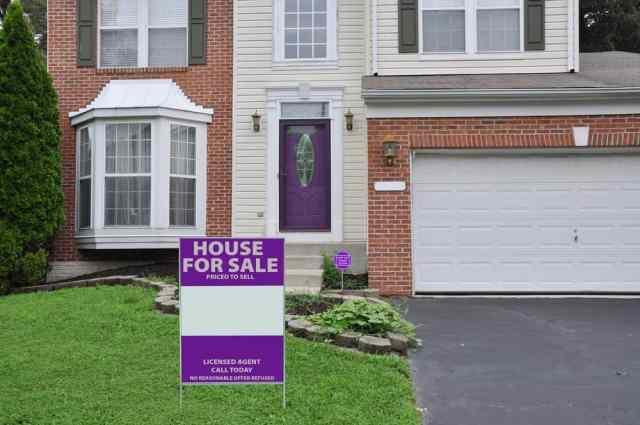 Bir banliyö evinin önünde bir ön çim Satılık Ev tabela.
