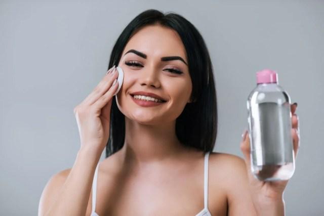 Yüzünü makyaj temizleyiciyle temizleyen bir kadın.