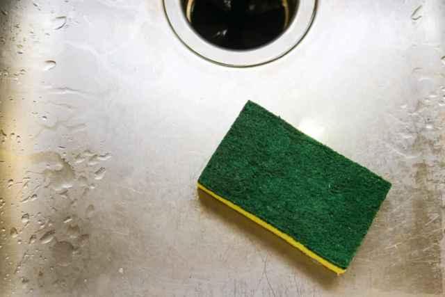 Paslanmaz çelik lavabo üzerinde yeşil ve sarı bir bulaşık süngeri.
