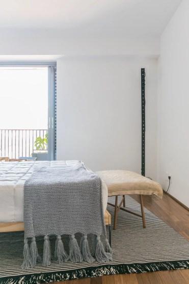 Tapete listrado de tear no pé da cama | Foto: Histórias de Casa